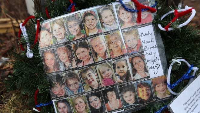 Photos of victims are placed near the Sandy Hook Elementary School a month after the Newtown, Conn., mass shooting.