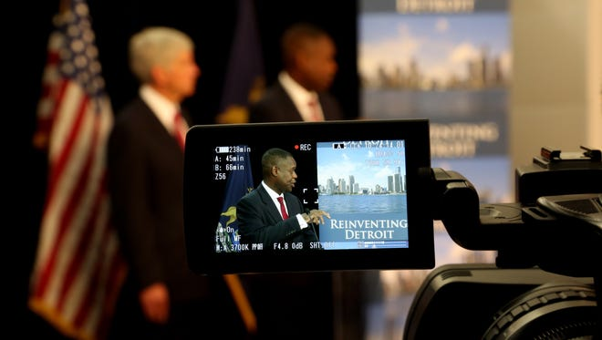 Detroit Emergency Manager Kevyn Orr is seen through the LCD screen of a video camera belonging to a Canadian TV station during a press conference on Friday, July 19, 2013 in Detroit.