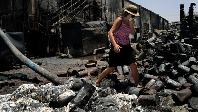 A Jewish tourist from Germany covers her face as she walks in a paint factory damaged by Saturday's rockets fired by Palestinian militants from the Gaza Strip, in the southern Israeli town of Sderot, Sunday.