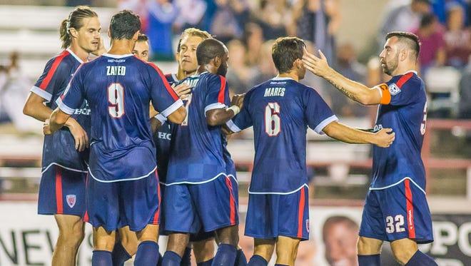 Eleven players celebrate a first-half goal against Carolina.
