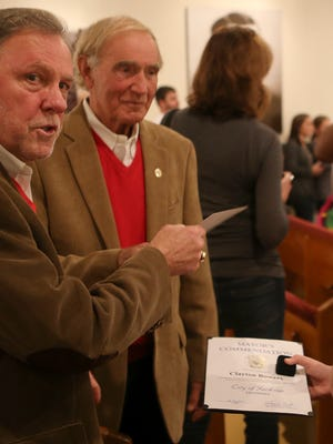 "Madison County Mayor Jimmy Harris, left, and Jackson Mayor Jerry Gist, center, look at a picture with Clayton Bowers after the ""Cookies & Story Time with Santa"" event at the Casey Jones Museum on Saturday, Dec. 12, 2015. The event was hosted by the Madison County Imagination Library to celebrate their 10th anniversary."