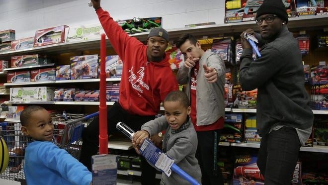 Detroit's Chuckie Clark, 8, and Carlos Clark, 9, pose with Kenny Demens, back left, volunteer Zain Alsaadi and fomer Michigan QB Devin Gardner.