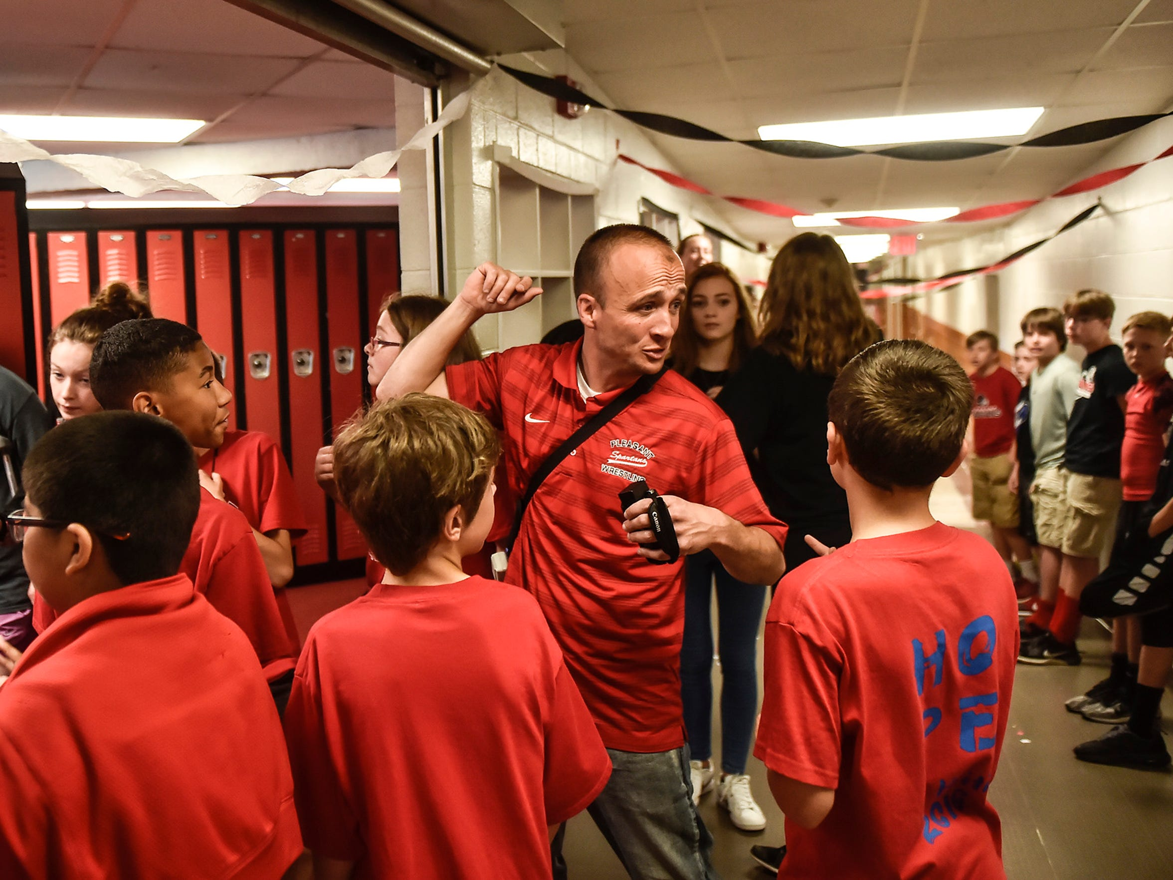 Joe Robinson, a seventh-grade social studies teacher at Pleasant Middle School, directs students during the filming of a lip dub video celebrating the 100th anniversary of the middle school building.
