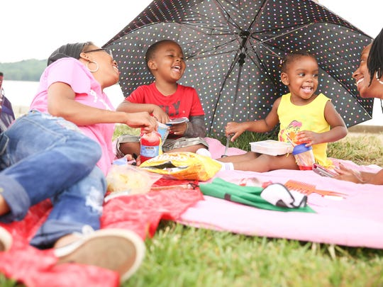 From left, Treva Corley, Amarri Corley, Amiya Corley and Kimberly Evans have a picnic in the shade at Percy Priest Lake in Nashville, Tenn.