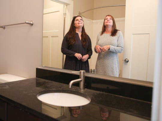 From left, HND Relator Marcia Creecy and home buyer Jill Molteni admire the bathroom lighting in Molteni's condominium at The Park at Melrose Heights.