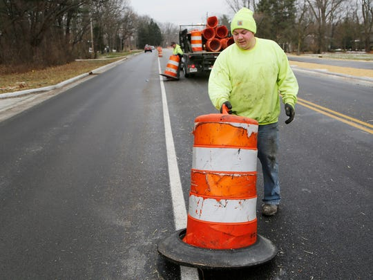 Taylor Bray removes a traffic barrel as Happy Hollow Road is prepared to open for two way traffic Friday, December 23, 2016, in West Lafayette. Bray is with Highway Safety Services.