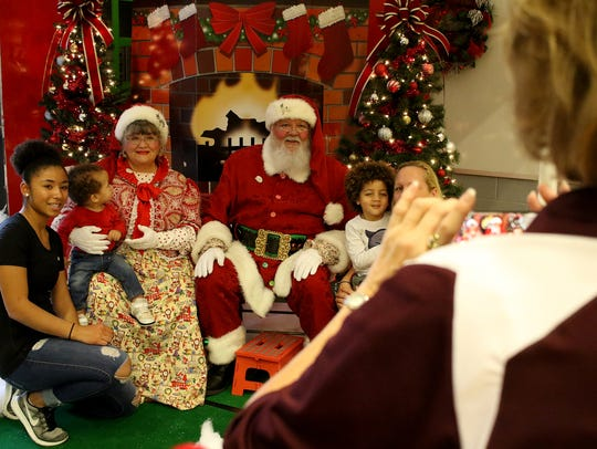 A family has their photo taken with Mr. and Mrs. Claus