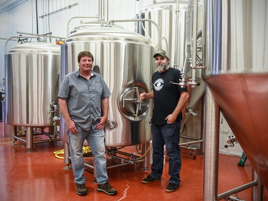 Kyle Kiefer and Tom Goebel stand near brewing equipment