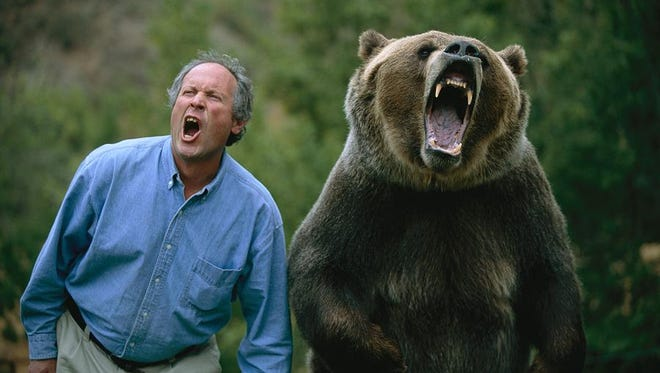 Douglas Chadwick and trained grizzly bear, Tank, snarl for the camera.