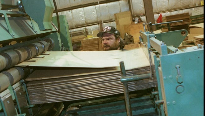 An archive photo from 1997 shows an H.P. Neun Co. employee at a flexo-folder-gluer machine when the company was located in Fairport.