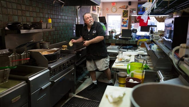 Bills' Cafe owner Bill Salley cooks in the kitchen of his restaurant on Tuesday, May 10, 2016, in Naples. Customers of the Third Avenue North restaurant have picked up on the owner's tradition of feeding the needy.