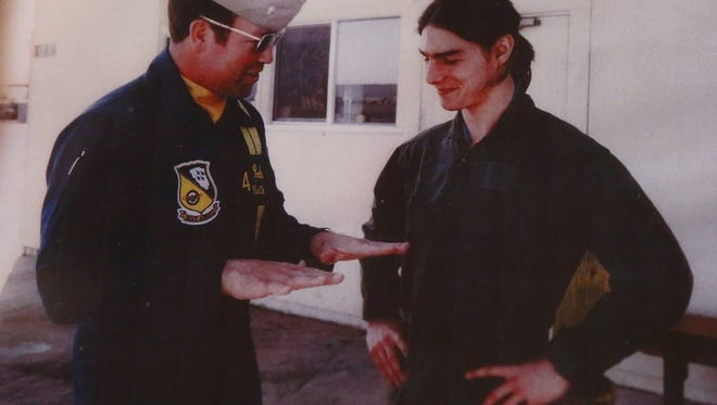 """Former Navy Blue Angel Curtis Watson, left, is shown in a photo from 1985, next to then-rising star Tom Cruise, center, after flying. Watson took the then-rising star actor, Cruise, in to preparation for his character development as Maverick. Top Gun was released May 16, 1986. Watson said he kept apologizing for his long hair """" his role in filming the movie Legend """" and kept calling him """"sir."""""""