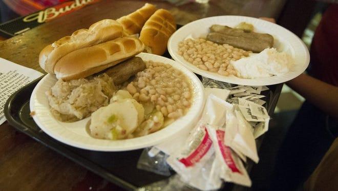 Plates of bratwurst, sauerkraut, beans and German potato salad sit on the bar during Germania Maennerchor Volksfest 2016 in Evansville on Friday.