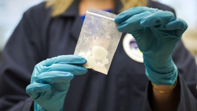 A bag of drugs that was seized in a raid is displayed at the Drug Enforcement Administration Special Testing and Research Laboratory in Sterling, Virginia. The DEA is setting up an office in China to work with Beijing to try to cut off the Chinese supply of deadly synthetic drugs, like fentanyl and carfentanil.