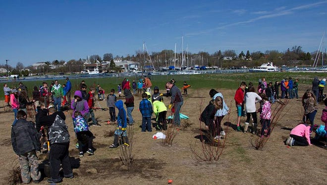 Students from Madison Elementary plant trees at the Manitowoc Containment.