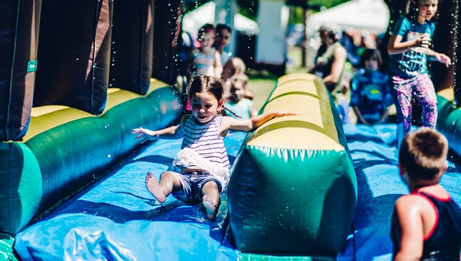 Kids enjoy the slip-and-slide at a past Pay It Forward Festival in Spring Hill. The 2017 festival is set for Saturday, Aug. 19, at the Children's Home in Spring Hill.