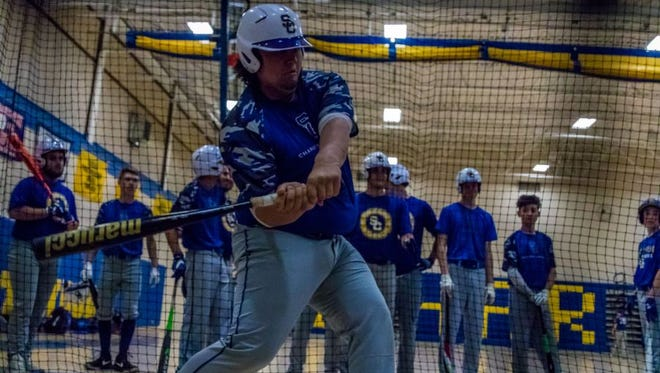 Spotswood catcher Mike Izzo takes some swings in the cage earlier this season.