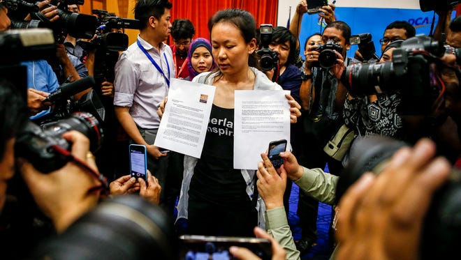 The wife of a missing Malaysia Airlines Flight MH370 passenger shows a press statement to reporters at a media conference room in Putrajaya, Malaysia, on Jan. 29.