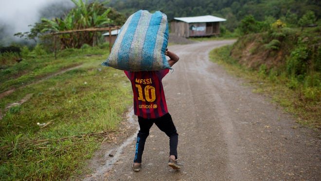 Jhorlis Huallpa, 17, carries a bagful of tarps, to be used for drying coca leaves, in La Mar, province of Ayacucho, Peru.