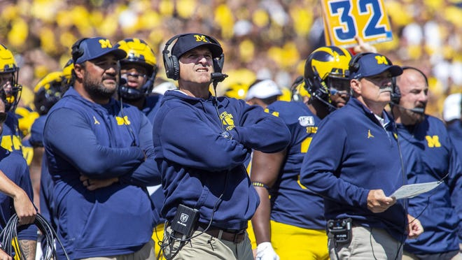 Michigan head coach Jim Harbaugh, center, is 0-5 against archrival Ohio State. When will they play each other again? Later this fall? Next spring? Or not until 2021?
