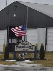 A flag is flown at half mast on Friday at Pagel's Ponderosa Dairy in Kewaunee. CEO John Pagel and his son-in-law Steve Witcpalek were among those killed when their Green Bay-bound plane crashed Thursday night in Indiana.