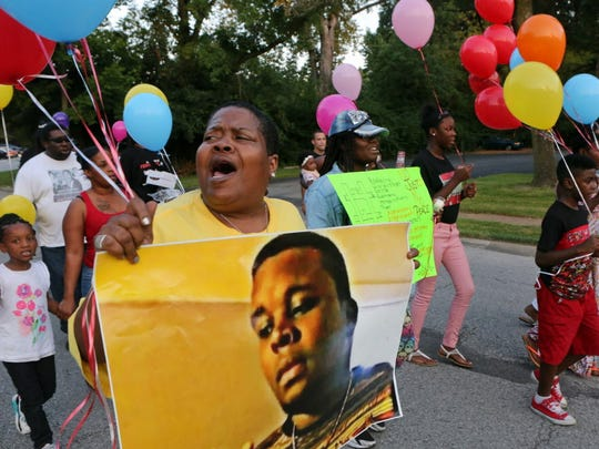 Sharon Cowan chants as she marches on the way to a candle light vigil to mark the two-year anniversary of the police shooting death of Michael Brown in Ferguson, Mo. The family of Brown settled a federal wrongful death lawsuit with the city of Ferguson on Tuesday, June 20, 2017.