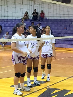 Sia Duenas, Samyra Quinata (24) and Jasmine Almoguera (16) prepare at the net during their IIAAG girls' volleyball league matchup against the Okkkodo Bulldogs on Friday night.