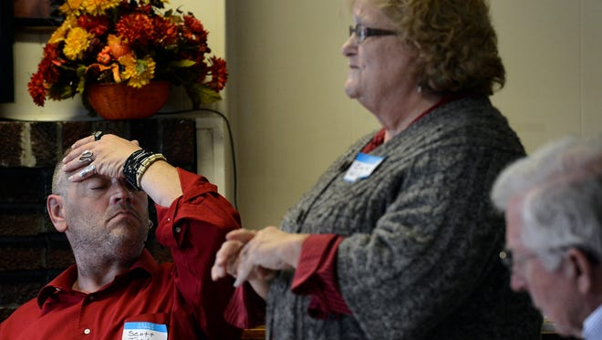 Scott Tedder, left, listens to Cathie Williams talk about how her daughter, Tammy Summers was shot in 2009 while at their church. Williams spoke during a gun violence survivor panel discussion at the Corinthian Missionary Baptist Church on Saturday, Nov. 21, 2015 in Nashville, Tenn. Cathie Williams' daughter recovered from her injuries. Scott Tedder was shot in the head when he was 11-years-old while sleeping in his bed.