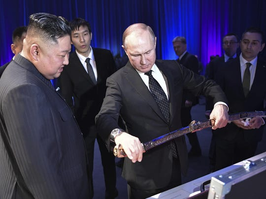 Russian President Vladimir Putin, right, delivers a present of a Russian saber to North Korea's leader Kim Jong Un during their meeting in Vladivostok, Russia, Thursday, April 25, 2019.