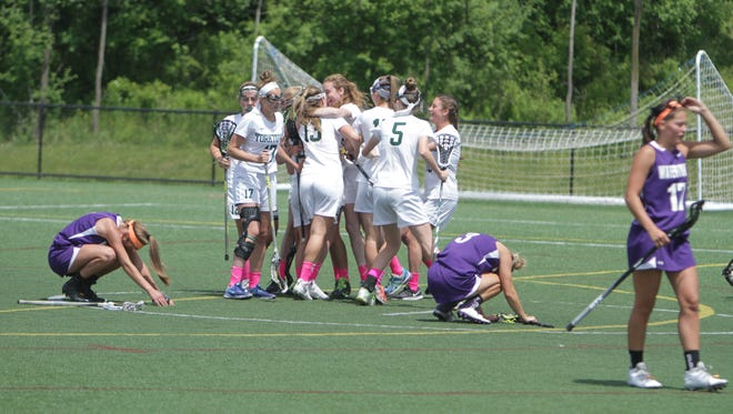 Yorktown mobs Casey Duff after her game-winning overtime goal against Watertown in a New York State girls lacrosse Class B state semifinal game at Tompkins Cortland Community College  in Dryden on Friday, June 10th, 2016. Yorktown won 10-9.