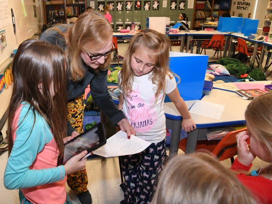 Tammy McDorman, a second-grade teacher at Fowler Elementary, helps direct her students in an iPad quick read (QR) code scavenger hunt Friday morning during the school's Read 2 Learn rally.