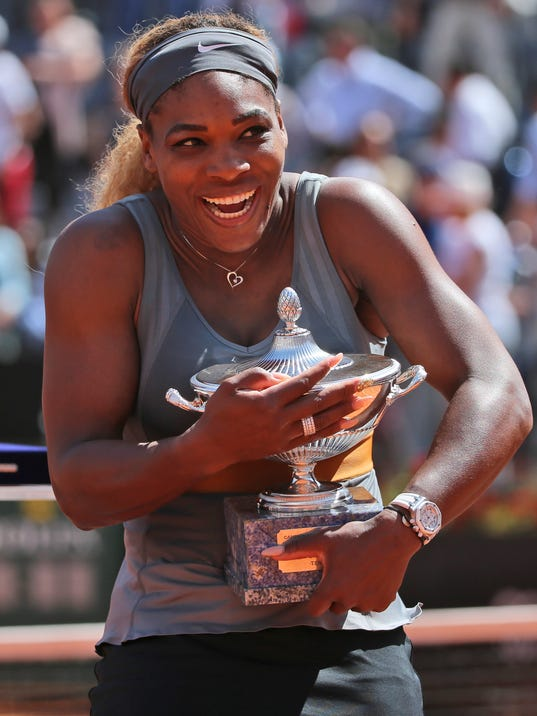 Serena Williams smiles as she holds the trophy after winning the final match against Italy's Sara Errani at the Italian open tennis tournament in Rome, Sunday, May 18, 2014. Serena Williams kept the crowd from being a factor in a 6-3, 6-0 victory over 10th-seeded Sara Errani to win the Italian Open for the third time Sunday. (AP Photo/Gregorio Borgia)