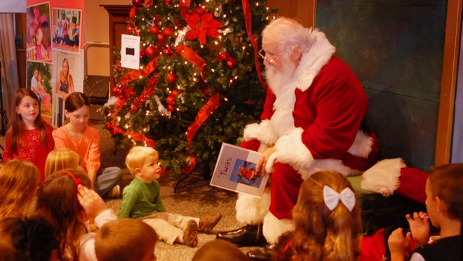 "Santa Claus, as portrayed by Will Davis, reads ""Twas the Night Before Christmas"" to children gathered at The Santa Experience at Sunday's 2014 Festival of Trees, hosted by the Junior League of South Brevard, Inc."