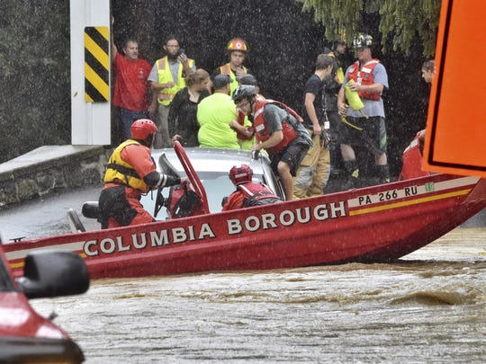A man is rescued from an SUV on Bridge Valley Road at Chiques Creek on Friday, Aug. 31, 2018, in West Hempfield Township, Lancaster County, Pa. A band of unusually heavy rain Friday afternoon over a swath of southcentral Pennsylvania closed roads and stranded vehicles on one of the busiest travel days of the year. (Blaine Shahan/LNP/LancasterOnline via AP)