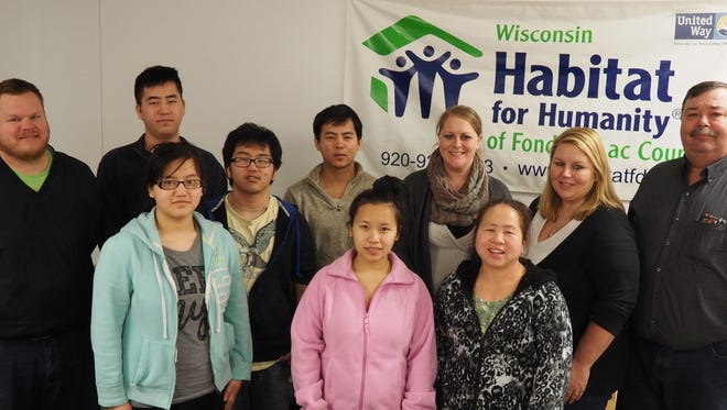 Back row, from left, are: Joel Boelhower, construction manager for Habitat; Chou Lee; Phia Lee; Tou  Lee; Jessica Lehman, board member and treasurer for Habitat; Julie Woznick, board president for Habitat; Tom Wilhelms, executive director for Habitat. Front row, from left, are: Yer Lee; Mee Xiong, and La Xiong.