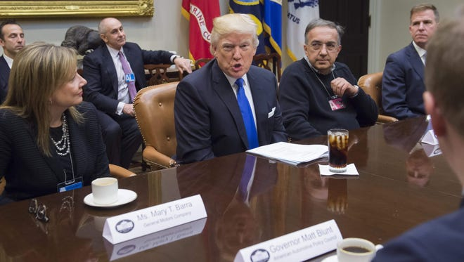 President Donald Trump speaks alongside General Motors CEO Mary Barra (L) and Fiat Chrysler CEO Sergio Marchionne (2nd R) during a meeting withautomobile industry leaders in the Roosevelt Room of the White House in Washington, DC, January 24, 2017. / AFP PHOTO / SAUL LOEBSAUL LOEB/AFP/Getty Images