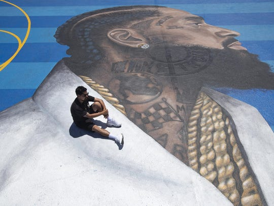 "Gustavo Zermeno Jr. said it was a ""no brainer"" to paint the mural of Nipsey Hussle at a basketball court near the rap artist's clothing store. About 50 such memorials have popped up in Los Angeles."