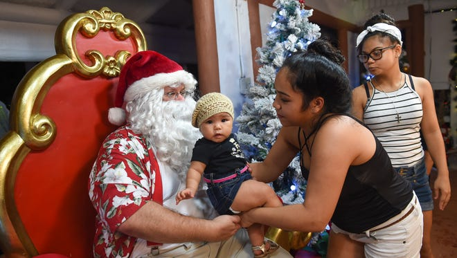 Children posed for pictures with Santa Claus during the Magof Nochebuena Peace Festival 2017 at the Government House on Dec. 2, 2017.