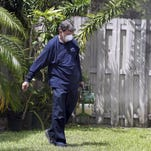 A mosquito control inspector sprays pesticide in Miami on April 12, 2016.