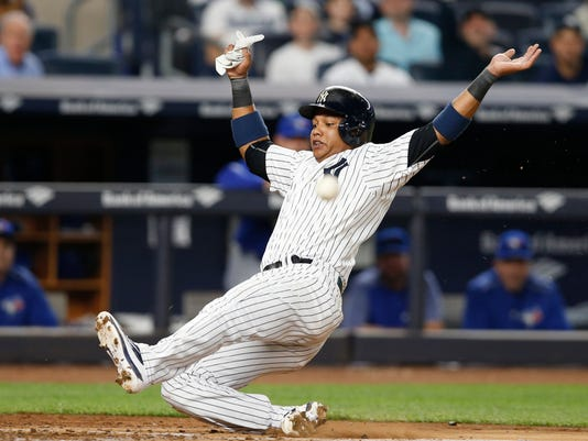 New York Yankees Starlin Castro slides toward home plate as the throw on Aaron Judge's RBI single comes simultaneously during the fourth inning of a baseball game against the Toronto Blue Jays, in New York, Monday, May 1, 2017. Castro beat the throw to score a run on the play. (AP Photo/Kathy Willens)