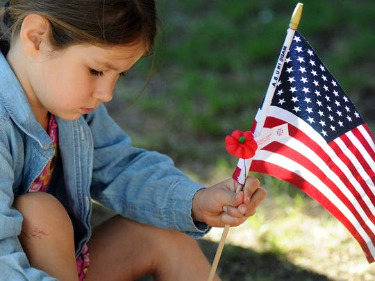 Eve Ward of Las Cruces holds a flag and poppy at a recent Memorial Day ceremony in Las Cruces. The red poppy is a remembrance of the lives lost in World War I and all conflicts since.
