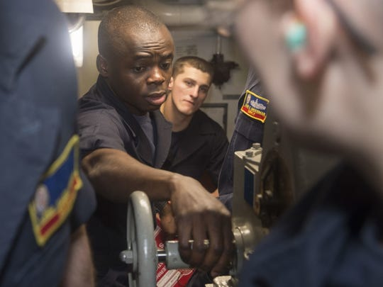 Navy Petty Officer 2nd Class Dominic Mando, from North Brunswick,explains how to engage the trickwheel in aft steering during a loss of steering drill aboard the amphibious assault ship USS Bonhomme Richard (LHD 6). Bonhomme Richard, flagship of the Bonhomme Richard Expeditionary Strike Group (ESG), is operating in the Indo-Asia-Pacific region to enhance partnerships and be a ready-response force for any type of contingency.