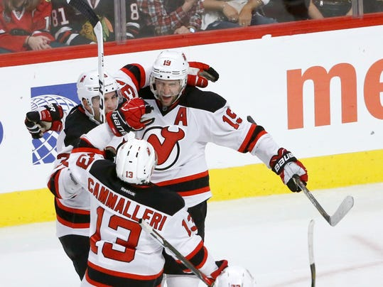 New Jersey Devils' Travis Zajac (19) celebrates his third goal of the game with Michael Cammalleri (13) and Yohann Auvitu during the third period of an NHL hockey game against the Chicago Blackhawks on Thursday, Dec. 1, 2016, in Chicago. The Blackhawks won 4-3 in overtime. (AP Photo/Charles Rex Arbogast)
