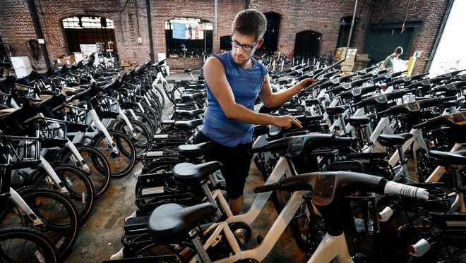 Taylor Desjardius helps assemble 600 for-rent bicycles and 60 docking stations that will be placed around the city before Explore Bike Share's May 23 launch.