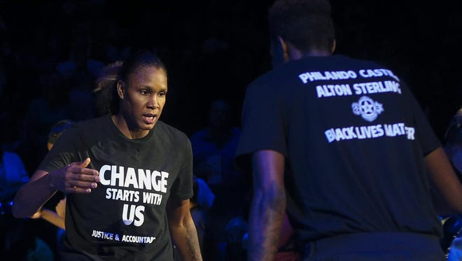 Minnesota Lynx forward Rebekkah Brunson, left, is greeted by Minnesota Lynx forward Natasha Howard while starting lineups are announced on July 9 at the Target Center in Minneapolis. The Lynx donned black T-shirts before the game in remembrance of two men who were shot by police and the five Dallas police officers who were killed in an attack last week.