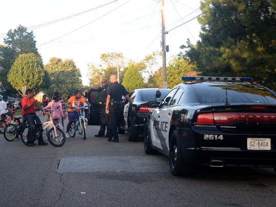 Children ride their bikes with two Jackson police officers at a block party on Lincoln Street during Jackson's 2014 National Night Out. The 2019 event will be held Tuesday, Oct. 1.