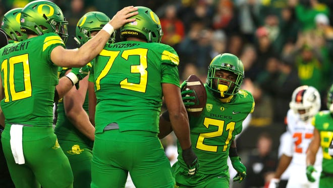 Nov 25, 2017; Eugene, OR, USA; Oregon Ducks running back Royce Freeman (21) celebrates a touchdown with quarterback Justin Herbert (10) and offensive lineman Tyrell Crosby (73) against the Oregon State Beavers in the first quarter at Autzen Stadium. Mandatory Credit: Scott Olmos-USA TODAY Sports