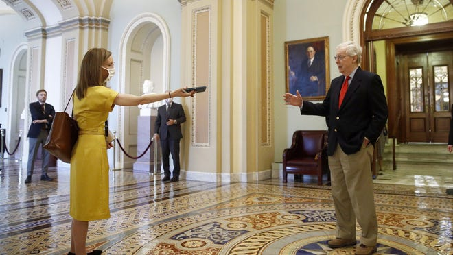 """Senate Majority Leader Mitch McConnell of Ky., right, speaks with a reporter outside the Senate chamber on Capitol Hill in Washington, Thursday, April 9, 2020. Senate Democrats on Thursday stalled President Donald Trump's request for $250 billion to supplement a """"paycheck protection"""" program for businesses crippled by the coronavirus outbreak, demanding protections for minority-owned businesses and money for health care providers and state and local governments."""