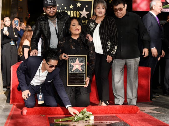 Chris Perez, bottom left, the former husband of the late singer Selena Quintanilla, puts flowers down on her new star on the Hollywood Walk of Fame as he poses with, left to right, Selena's brother A.B. Quintanilla III, her sister Suzette, and her parents Marcella Ofelia Samora and Abraham Quintanilla Jr. during a posthumous star ceremony on the Hollywood Walk of Fame on Friday, Nov. 3, 2017, in Los Angeles. (Photo by Chris Pizzello/Invision/AP)