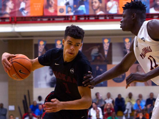 Mokan Elite player Michael Porter Jr., left, drives to the basket while being defended by PSA Cardinals player Deng Gak during the first half of the Nike Peach Jam Finals at Riverview Park Activity Center in July.